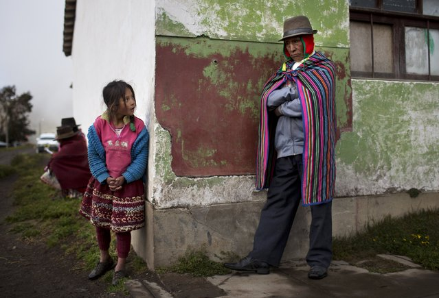 A girl looks around a corner at a self-defense force member during a meeting about security for the next day's general election in Uchuraccay, Peru, Saturday, April 9, 2016. (Photo by Rodrigo Abd/AP Photo)
