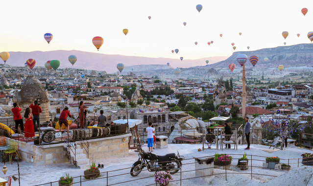 Tourists take photos of hot air balloons glide over the historical Cappadocia region from their hotel's terrace, in Central Anatolia's Nevsehir province, Turkey on June 29, 2019. Cappadocia is preserved as a UNESCO World Heritage site and is famous for its chimney rocks, hot air balloon trips, underground cities and boutique hotels carved into rocks. When weather conditions reach ideal level, 150 hot-air balloons launch every morning at Cappadocia. Tourists view the geographical region formed by interactions of wind and rain with lavas erupted from Mount Erciyes and Hasan. (Photo by Behcet Alkan/Anadolu Agency/Getty Images)