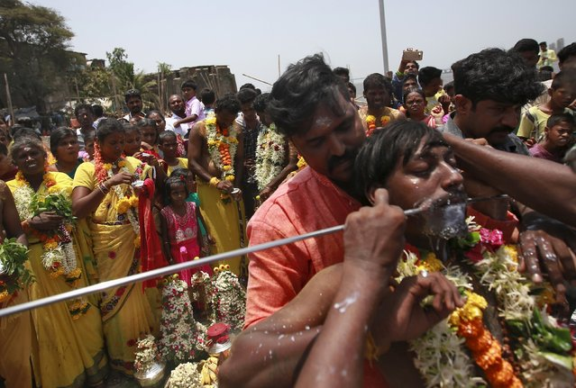 A devotee gets his mouth pierced with a trident as others watch during a religious procession dedicated to Goddess Mariamman in Mumbai, India, April 19, 2016. (Photo by Danish Siddiqui/Reuters)