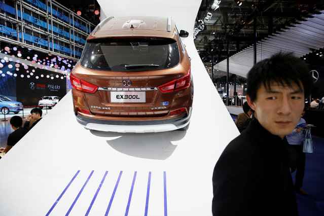 People gather around vehicles presented at Beijing Automotive Group (BAIC) booth during Auto China 2016 auto show in Beijing April 25, 2016. (Photo by Damir Sagolj/Reuters)