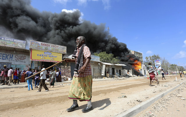 Somali traders attempt to evacuate their goods from their shops near a burning petrol station in Hodan district of Somalia's capital Mogadishu, April 10, 2014. (Photo by Feisal Omar/Reuters)