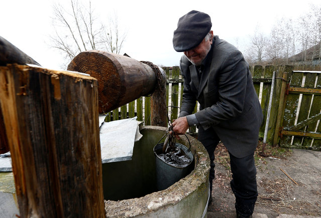 Ivan Shamyanok, 90, takes water from a well at his house in the village of Tulgovichi, near the exclusion zone around the Chernobyl nuclear reactor, Belarus April 2, 2016. The zone is 1,615 miles or roughly the size of Luxembourg. He and his wife turned down the offer to relocate and never felt any ill effects from the radiation. (Photo by Vasily Fedosenko/Reuters)
