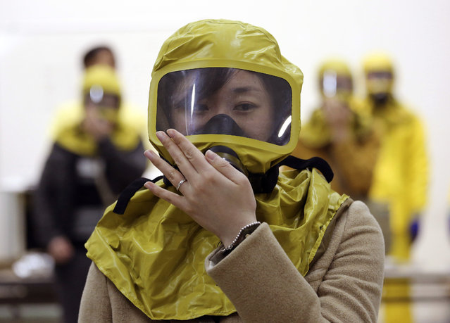 A South Korean government official checks her gas mask during a civil defense drill against possible North Korea's chemical attack at their office in Seoul, South Korea, Wednesday, March 15, 2017. A nationwide civil defense drill took place Wednesday preparing for possible terror, natural disaster and sudden air attack by North Korea. (Photo by Ahn Young-joon/AP Photo)
