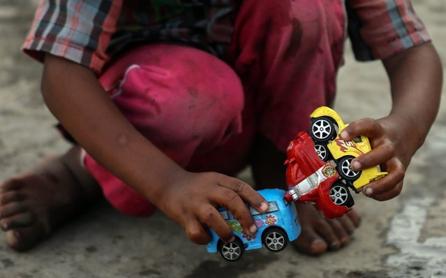 A child of a farmer from the drought affected districts of Maharashtra plays with the toy car at a temperory refugee camp in Mumbai, India, 26 April 2016. According to reports, 21 districts in Maharashtra are drought-affected. Hundreds of people are staying in a refugee camp in Mumbai, migrated from the drought affected area in Maharashtra. (Photo by Divyakant Solanki/EPA)