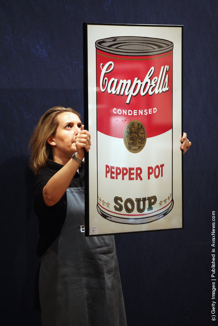 A gallery assistant holds a print of an Andy Warhol artwork entitled Campbell's Soup I: Pepper Pot estimated to fetch 10,000 GBP in Bonhams auction house
