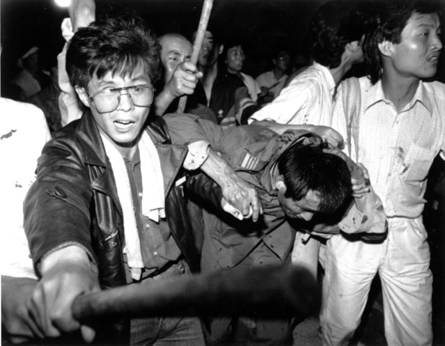 A captured tank driver is helped to safety by students as the crowd beats him June 4, 1989. This year marks the 10th anniversary of the bloody June 4 1989 army crackdown on the pro-democracy movement at Beijing's Tiananmen Square. (Photo by Reuters/China Stringer Network)
