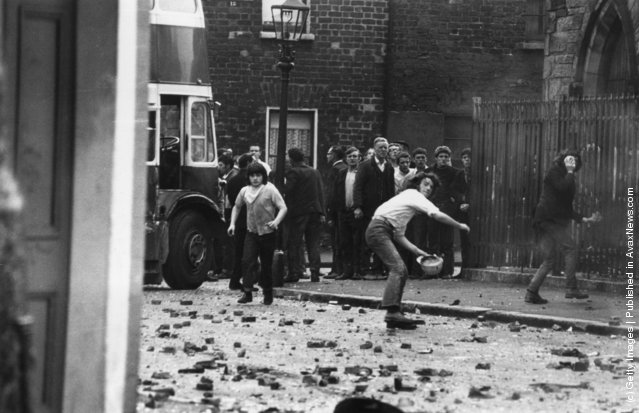 Young men throwing stones at the Royal Ulster Constabulary (RUC)  in the Falls Road area of Belfast. Five Catholics were killed, 60 injured and hundreds of homes devastated after armed British soldiers attempted to impose a curfew