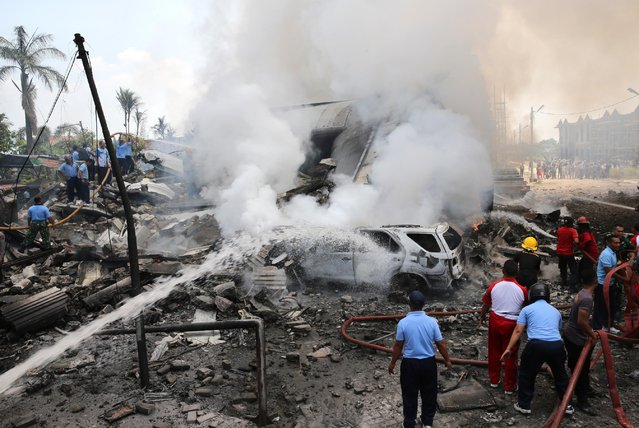Rescuers spray water at the wreckage of an air force cargo plane that crashed in Medan, North Sumatra, Indonesia, Tuesday, June 30, 2015. (Photo by AP Photo/Hafiz)
