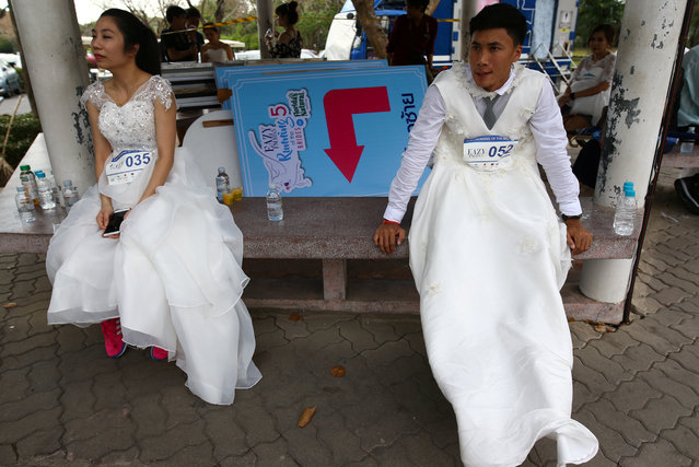 """Couples participate in the """"Running of the Brides"""" race in a park in Bangkok, Thailand March 25, 2017. (Photo by Athit Perawongmetha/Reuters)"""