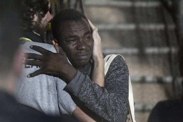 In this photo taken on Tuesday, August 20, 2019 a man cries as he hugs a crew member after disembarking from the Open Arms rescue ship on the Sicilian island of Lampedusa, southern Italy. An Italian prosecutor ordered the seizure of a rescue ship and the immediate evacuation of more than 80 migrants still aboard, capping a drama Tuesday that saw 15 people jump overboard in a desperate bid to escape deteriorating conditions on the vessel and Spain dispatch a naval ship to try to resolve the crisis. (Photo by Salvatore Cavalli/AP Photo)