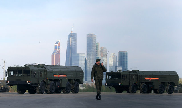 """A Russian serviceman walks past Russian Iskander-M missile launchers before a rehearsal for the Victory Day parade, with the Moscow International Business Center also known as """"Moskva-City"""" seen in the background, at a range in Moscow, Russia, May 5, 2016. (Photo by Maxim Shemetov/Reuters)"""