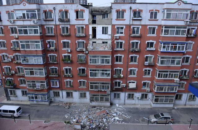 A policeman looks out from an apartment building where the balconies of two units on the seventh and the sixth floor fell off, in Shenyang, Liaoning province, China, July 6, 2015. The balcony of the unit on the fifth floor was also damaged during the incident which occurred on Monday afternoon at the 13-year-old residential building in northern China's city of Shenyang. No one was injured according to local media. (Photo by Reuters/Stringer)