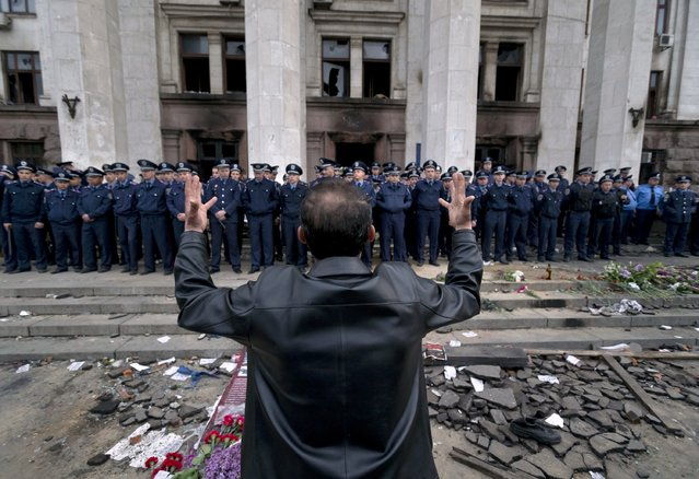 A man shouts as he gestures in front of police troops guarding the burnt trade union building in Odessa, Ukraine, Saturday, May 3, 2014, where more than 30 people died trying to escape during clashes the day before. Odessa had been largely tranquil since the February toppling of President Viktor Yanukovych, who fled to Russia. (Photo by Vadim Ghirda/AP Photo)