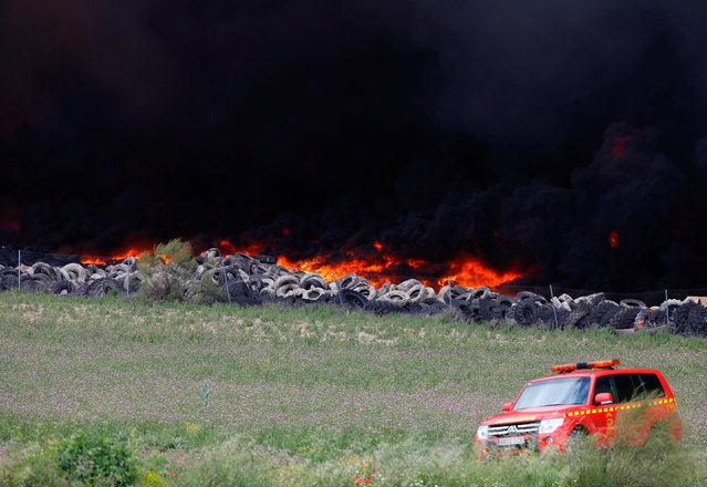 An emergency car stands near a fire at a tire dump near a residential development in Sesena, south of Madrid, Spain, May 13, 2016. (Photo by Sergio Perez/Reuters)