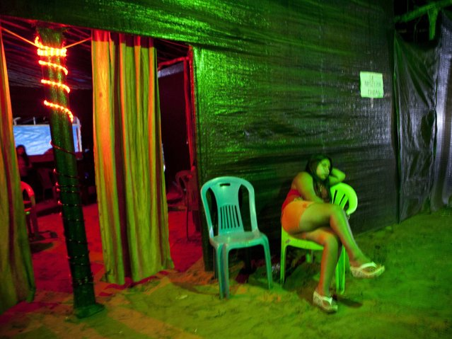 A s*x worker who is employed at an informal bar waits for customers in La Pampa in Peru's Madre de Dios region. Life is cheap in the mining camps. Deaths go unrecorded and the mercury miners use to bind gold flecks compounds the risks. Tons of the toxic metal have been dumped into rivers, contaminating fish, humans and other animals and plants. (Photo by Rodrigo Abd/AP Photo)