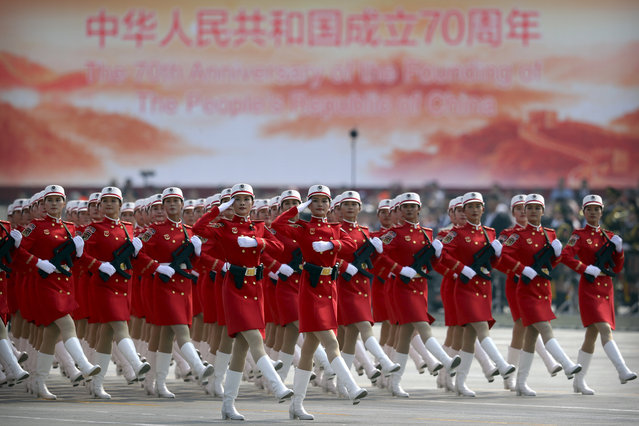 Chinese female militia members march in formation during a parade to commemorate the 70th anniversary of the founding of Communist China in Beijing, Tuesday, October 1, 2019. Trucks carrying weapons including a nuclear-armed missile designed to evade U.S. defenses rumbled through Beijing as the Communist Party celebrated its 70th anniversary in power with a parade Tuesday that showcased China's ambition as a rising global force. (Photo by Mark Schiefelbein/AP Photo)