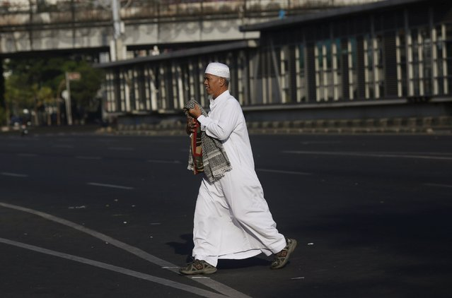 Muslims man carries his prayer mat after attending a mass Eid al-Fitr prayer on a street in Jakarta, Indonesia July 17, 2015. (Photo by Nyimas Laula/Reuters)