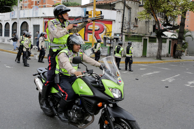 Riot police officers clash with opposition supporters in a rally to demand a referendum to remove President Nicolas Maduro in Caracas, Venezuela, May 18, 2016. (Photo by Marco Bello/Reuters)