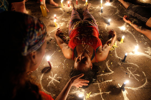 In this photo taken October 11, 2019, a woman surrounded by candles and designs drawn on the ground with white powder lies with her eyes closed during a spiritual ceremony on Sorte Mountain where followers of indigenous goddess Maria Lionza gather annually in Venezuela's Yaracuy state. Believers often ask for spiritual healing or protection from witchcraft, or thank the goddess for curing an illness. (Photo by Ariana Cubillos/AP Photo)