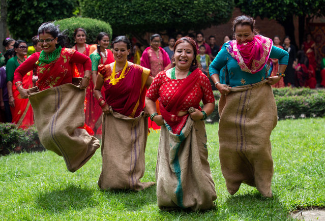 Women of the non-profit organization Maiti Nepal, a Rehabilitation and Orphanage home for HIV affected and trafficking women and children, play during a function to celebrate Teej festival in Kathmandu, Nepal, 29 August 2019. Maiti Nepal organized the event to help HIV positive and trafficking women and children and educate about the festival. The Teej festival is the biggest festival for Nepalese Hindu women. During the festival married women take a fast for the long and prosperous life of their husbands and unmarried women celebrate to get a good one by fasting for a day. The Teej festival will be celebrated on 02 September. (Photo by Narendra Shrestha/EPA/EFE)