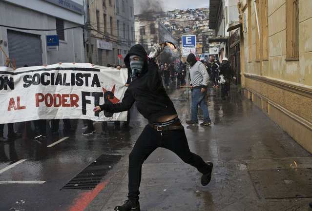 A masked protester launches a Molotov cocktail towards police, near Congress where President Michelle Bachelet was presenting the state-of-the-nation report, in Valparaiso, Chile, Saturday, May 21, 2016. (Photo by Esteban Felix/AP Photo)