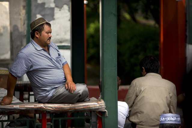 A Chinese Muslim man sits on a pillar as he waits for Eid al-Fitr prayers to begin at the Niujie mosque, the oldest and largest mosque in Beijing, Saturday, July 18, 2015. (Photo by Mark Schiefelbein/AP Photo)