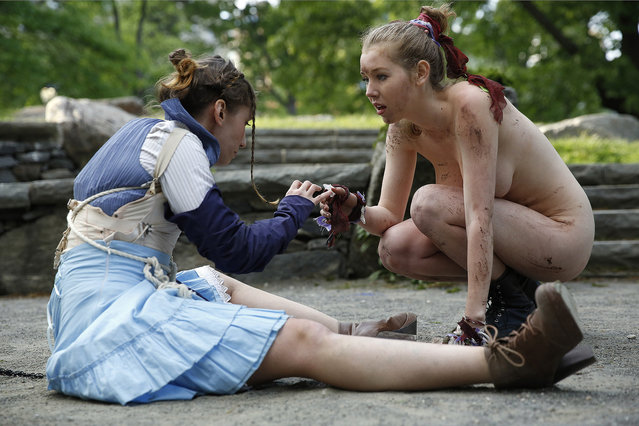 "Kara Lynn, left, as Ferdinand, and Marisa Roper, as Miranda perform at Summit Rock in Central Park during the Outdoor Co-Ed Topless Pulp Fiction theater company's production of Shakespeare's ""The Tempest"", Thursday, May 19, 2016, in New York. An all-female cast of 13 actors, dancers, and musicians perform in this a ""stripped-down"" production which has been for shorter running time. The production uses semi- and full-nudity to celebrate body freedom and free expression and to dramatize the conflict between the visitors to Prospero's island and its inhabitants. (Photo by Kathy Willens/AP Photo)"