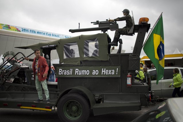 """A Brazil soccer fan performs on a vehicle where a mannequin soldier rides at the top and the side reads in Portuguese """"Brazil on the way to the sixth World Cup"""", referring to Brazil's five past World Cup titles and hope for a sixth this year, outside Arena Corinthians stadium in Sao Paulo, Brazil, Wednesday, June 11, 2014. (Photo by Rodrigo Abd/AP Photo)"""