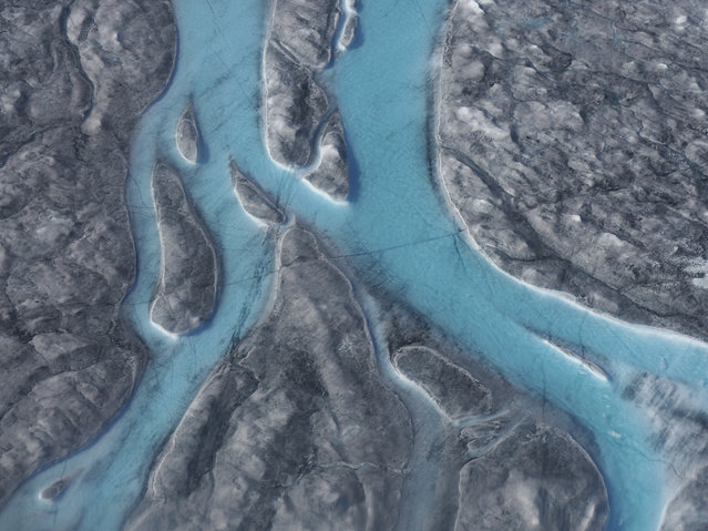 In this image taken on Thursday August 1, 2019 large rivers of melting water form on an ice sheet in western Greenland and drain into moulin holes that empty into the ocean from underneath the ice. The heat wave that smashed high temperature records in five European countries a week ago is now over Greenland, accelerating the melting of the island's ice sheet and causing massive ice loss in the Arctic. (Photo via Caspar Haarløv, Into the Ice via AP Photo)