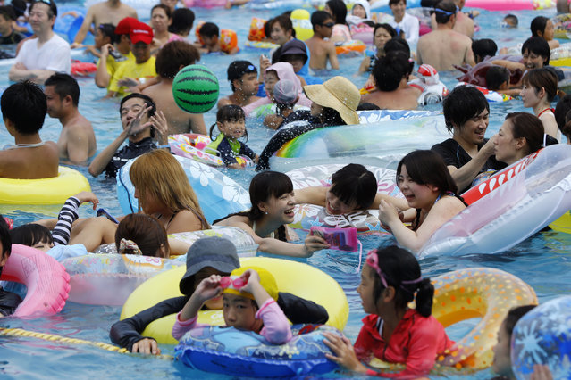 Visitors pack a giant pool at Toshimaen amusement park in Tokyo, Sunday, July 26, 2015. The temperature rose to 36 degrees Celsius (97 degrees Fahrenheit) in the Tokyo area.  Some 12,000 people are expected to visit the amusement park Sunday. (Photo by Shizuo Kambayashi/AP Photo)