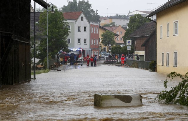 Local residents and firefighters stand in the flooded street in the Bavarian village of Triftern east of Munich, Germany, June 1, 2016. (Photo by Michaela Rehle/Reuters)