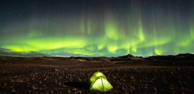 """""""Happy Camping"""". Camping beneath the beauty of the Aurora Borealis in Southern Iceland in the Fall of 2013. An odd sort of reflection with the tent and the sky happening. Photo location: Southern Iceland. (Photo and caption by David Whyte/National Geographic Photo Contest)"""
