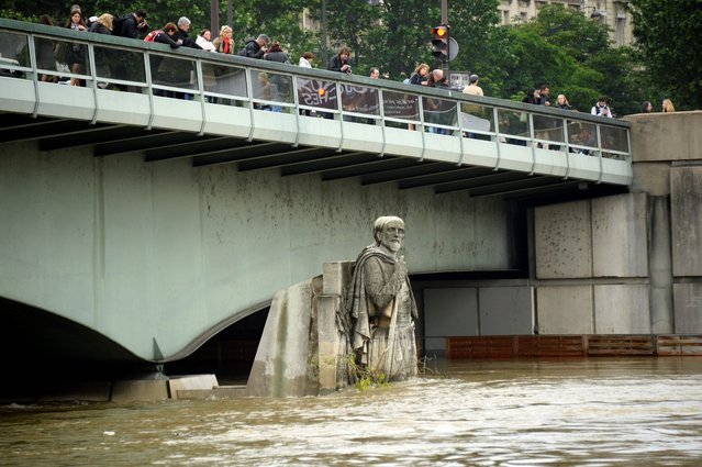 This picture taken on June 2, 2016 shows the Zouave statue of the Alma bridge flooded by the river Seine following heavy rainfalls in Paris. Torrential downpours have lashed parts of northern Europe in recent days, leaving four dead in Germany, breaching the banks of the Seine in Paris and flooding rural roads and villages. (Photo by Bertrand Guay/AFP Photo)