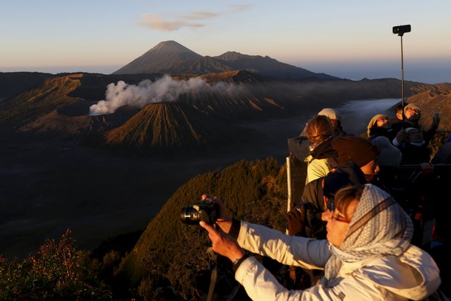 People take pictures of Bromo Tengger Semeru National Park during sunrise on top of Mount Pananjakan, ahead of Kasada festival in Indonesia's East Java province, July 31, 2015. The Kasada festival will be held on August 1, when the worshippers throw offerings such as livestock and other crops into the volcanic crater of Mount Bromo to give thanks to the Hindu gods for ensuring their safety and prosperity. (Photo by Reuters/Beawiharta)