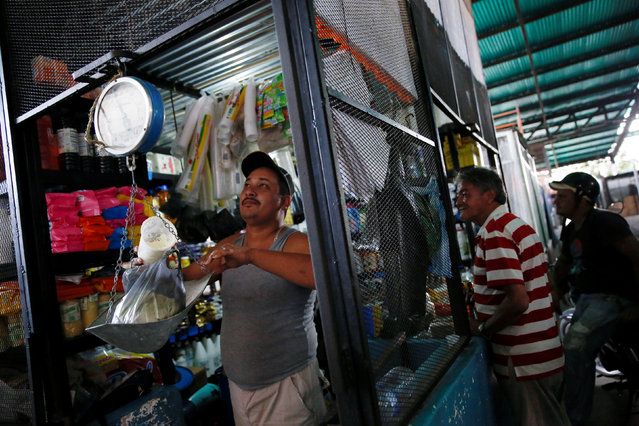 A man weighs milk powder that is made in Colombia, before selling it to his customers at a stall that sells basic food and staple items at a market in La Fria, Venezuela, June 2, 2016. (Photo by Carlos Garcia Rawlins/Reuters)