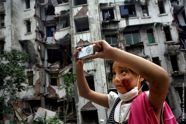 Nine-year-old Xia Xueyin, her face badly bruised during the earthquake, takes photos of her family's damaged home in Hanwang town of Sichuan province May 22, 2008