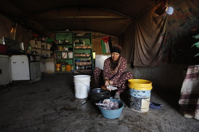 In this Tuesday, July 21, 2015, photo, a Palestinian woman cooks in her family tent in the village of Susiya, south of the West Bank city of Hebron. (Photo by Majdi Mohammed/AP Photo)