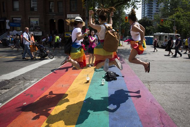 "Revelers jump on a rainbow painted crosswalk in Church Street, Toronto's LGBT neighbourhood, before ""WorldPride"", a gay pride parade, in Toronto, June 29, 2014. Toronto is hosting WorldPride, a week-long event that celebrates the lesbian, gay, bisexual and transgender (LGBT) community. (Photo by Mark Blinch/Reuters)"
