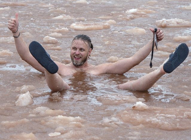 Revellers enjoy air temperatures near freezing as they participate in the annual New Year's polar bear dip in the icy waters of Charlottetown harbour on Wednesday, January 1, 2020, in Charlottetown, Prince Edward Island. (Photo by Andrew Vaughan/The Canadian Press via AP Photo)