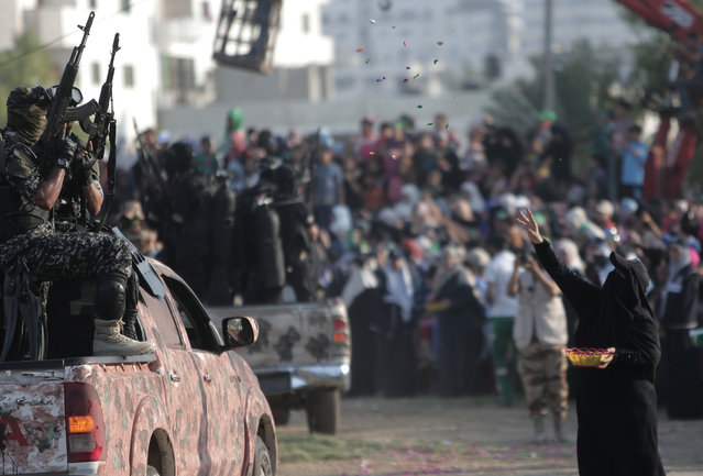 A Palestinian woman throws candy on Hamas masked gunmen with their guns during a graduation ceremony of the Hamas, Liberation Youth, military summer camp, in Gaza City, Wednesday, August 5, 2015. (Photo by Khalil HamraAP Photo)