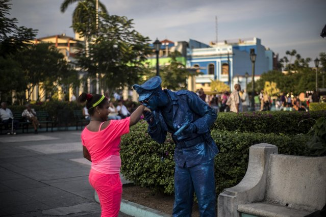In this March 22, 2015 photo, a street performer, dressed as a police statue, kisses a girl's hand after she gave him a coin in Santiago, Cuba. The number of private business licenses in Santiago grew to 34,000 as of February, according to government figures, thousands more than in previous years but still a fraction of the more than 120,000 in Havana. (Photo by Ramon Espinosa/AP Photo)