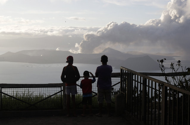 People watch from Tagaytay, Cavite province, south of Manila, as Taal Volcano continues to spew ash on Tuesday, January 14, 2020. Thousands of people fled the area through heavy ash as experts warned that the eruption could get worse and plans were being made to evacuate more. (Photo by Aaron Favila/AP Photo)