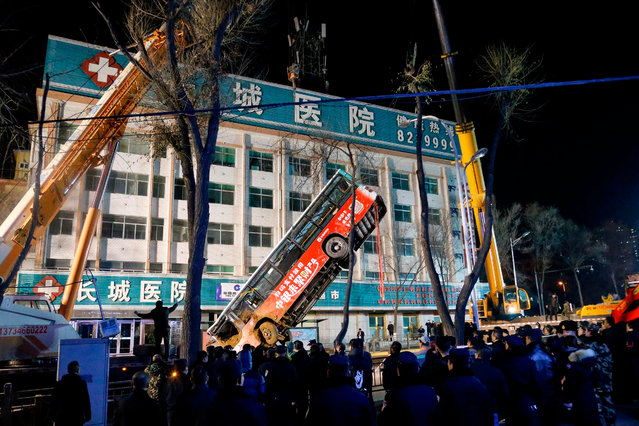 This photo taken on January 13, 2020 shows Chinese rescuers watching as a bus is lifted out after a road collapse in Xining in China's northwestern Qinghai province. An enormous sinkhole swallowed passers-by and a public bus in northwest China, reported state media on January 14, injuring fifteen people while another ten are still missing. (Photo by AFP Photo/China Stringer Network)
