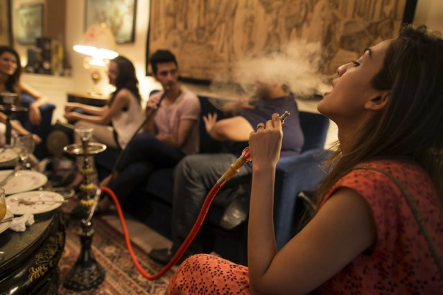 Sarah (R) and her brother, artist Usman Ahmed (2nd R), smoke a water pipe, also known as a narghile, as they sit with friends at home in Islamabad May 8, 2014. (Photo by Zohra Bensemra/Reuters)