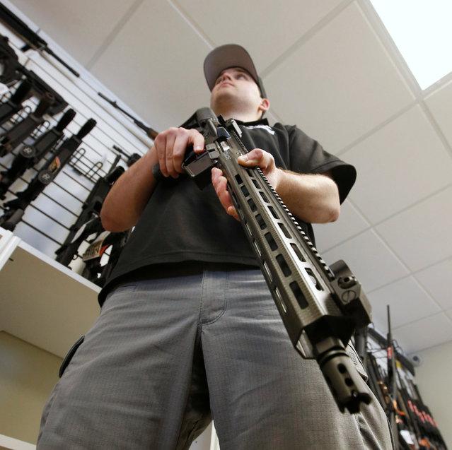 "Salesman, Ryan Martinez hold an AR-15 at the ""Ready Gunner"" gun store in Provo, Utah, U.S., June 21, 2016. (Photo by George Frey/Reuters)"
