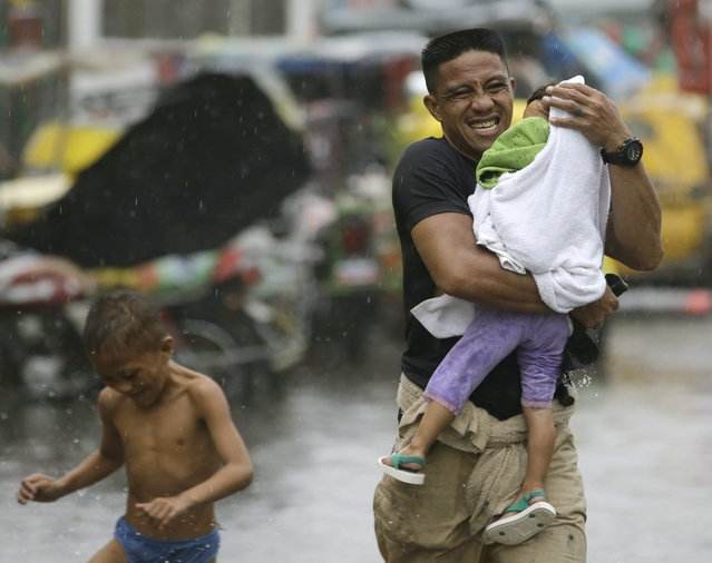 Residents at the slum community of Baseco evacuate to safer grounds at the onslaught of  Typhoon Rammasun (locally known as Glenda) which battered Manila Wednesday, July 16, 2014, in Manila, Philippines. Typhoon Rammasun left at least seven people dead and knocked out power in many areas but it spared the Philippine capital, Manila, and densely populated northern provinces from being directly battered Wednesday when its fierce wind shifted slightly away, officials said. (Photo by Bullit Marquez/AP Photo)
