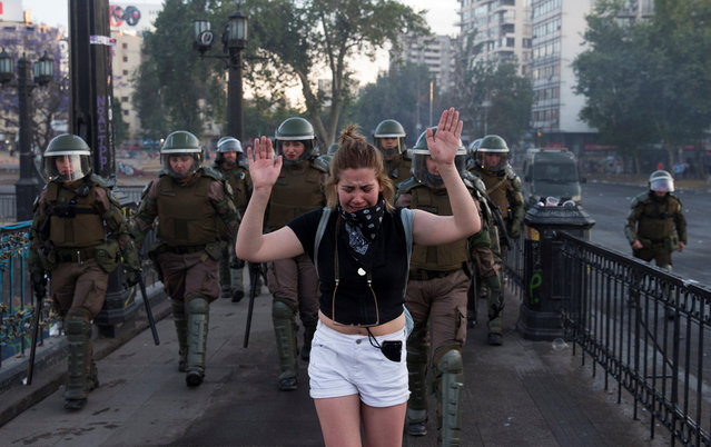 A woman cries while being escorted by police officers during an anti-government protest in Santiago, Chile, 07 November 2019. A proposed increase in the price of metro fares sparked a series of anti-government protests that have left at least 20 people dead. The protestors are demanding improvements in the quality of healthcare, education and general distribution of wealth in Chile. (Photo by Orlando Barría/EPA/EFE)