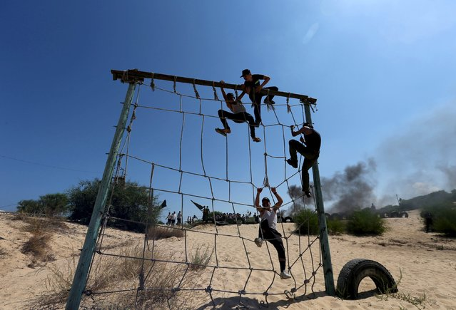Young Palestinians climb over a net during a military-style exercise at a summer camp organized by Islamic Jihad movement, in Khan Younis in the southern Gaza Strip, August 13, 2015. (Photo by Ibraheem Abu Mustafa/Reuters)