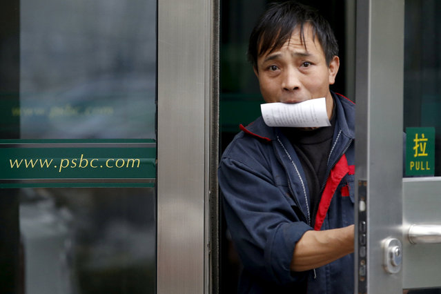 A man holding a receipt from an ATM machine in his mouth walks out of a branch of Postal Savings Bank of China (PSBC) in downtown Beijing, China, November 12, 2015. (Photo by Kim Kyung-Hoon/Reuters)