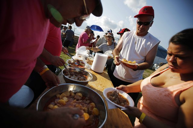 """Portuguese-Canadians are served stew during the intermission at an Azorean """"tourada a corda"""" (bullfight by rope) in Brampton, Ontario August 15, 2015. (Photo by Chris Helgren/Reuters)"""